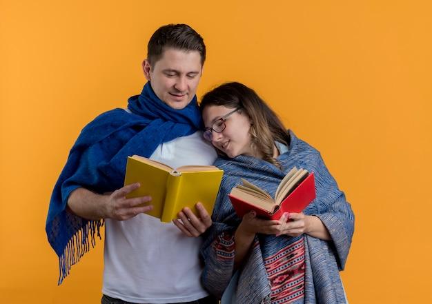 Casal jovem, homem e mulher, com cobertores segurando livros, feliz e positivo, sorrindo, juntos, em pé sobre uma parede laranja
