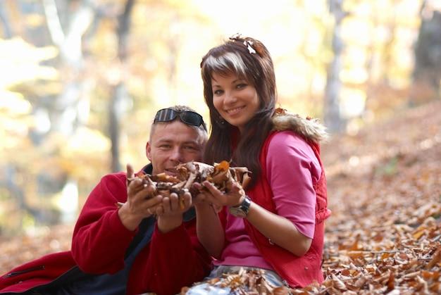 Casal jovem homem e mulher com folhas caindo na floresta de outono
