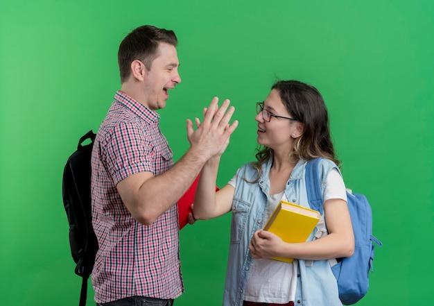 Casal jovem, homem e mulher com roupas casuais, com mochila segurando livros, dando high five sorrindo em pé sobre a parede verde