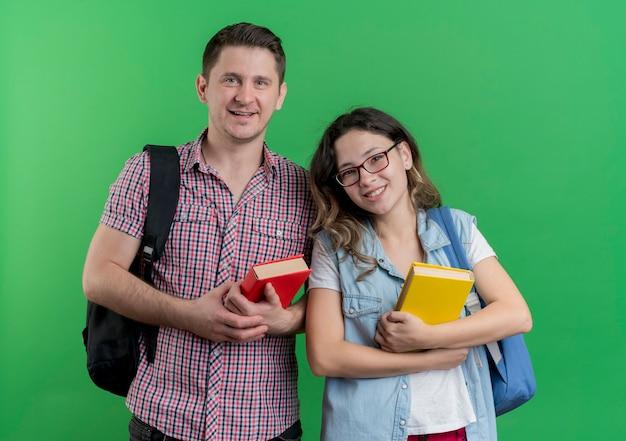 Casal jovem, homem e mulher com roupas casuais e mochilas segurando livros, sorrindo amigável em pé sobre a parede verde