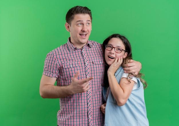 Casal jovem, homem e mulher com roupas casuais, felizes e positivos, sorrindo sobre o verde