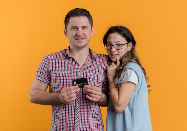 Casal jovem, homem e mulher com roupas casuais, homem feliz, mostrando o cartão de crédito ao lado da namorada na parede laranja