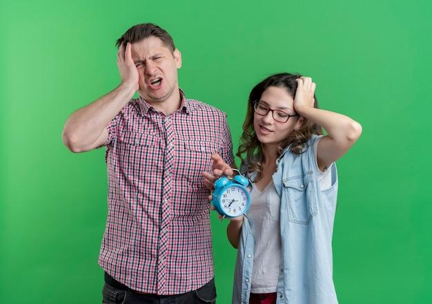 Casal jovem, homem e mulher com roupas casuais, segurando um despertador, parecendo confuso em pé sobre a parede verde