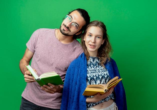Casal jovem, homem e mulher, com um cobertor segurando livros, sorrindo, em pé sobre a parede verde