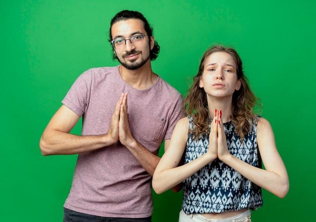 Casal jovem, homem e mulher, de mãos dadas em gesto namastê, como orando em pé sobre uma parede verde