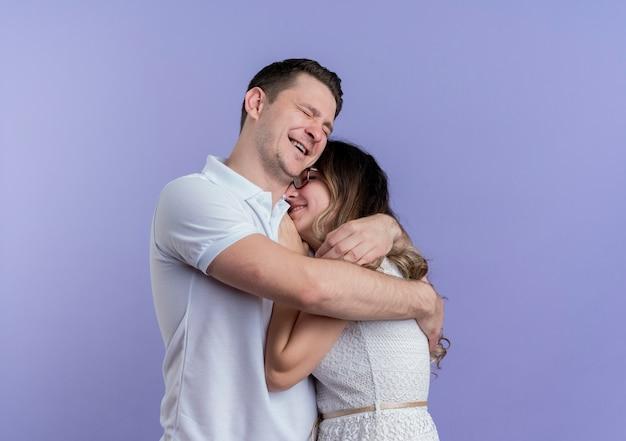 Casal jovem, homem e mulher, felizes e apaixonados se abraçando sobre o azul