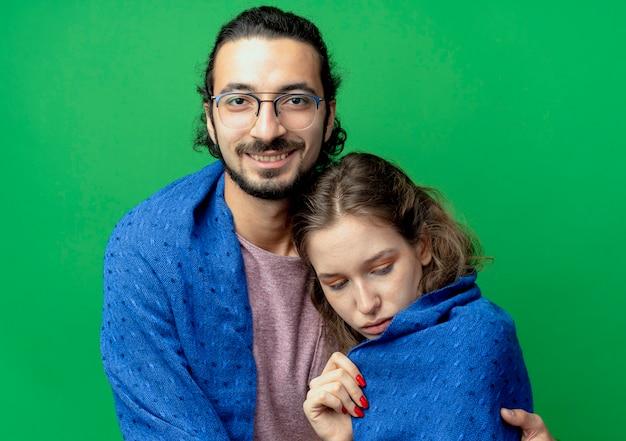 Casal jovem, homem e mulher, homem feliz abraçando sua amada namorada, sorrindo enquanto a envolve em um cobertor quente em pé sobre um fundo verde
