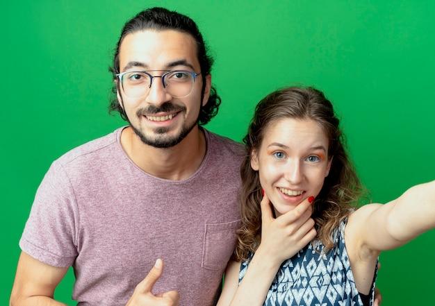 Casal jovem, homem e mulher, olhando para a câmera sorrindo com rostos felizes em pé sobre um fundo verde