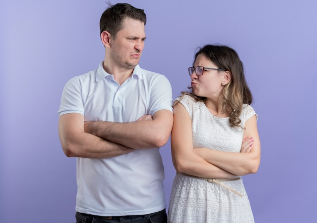 Casal jovem, homem e mulher, olhando um para o outro, carrancudo e com os braços cruzados em pé sobre a parede azul