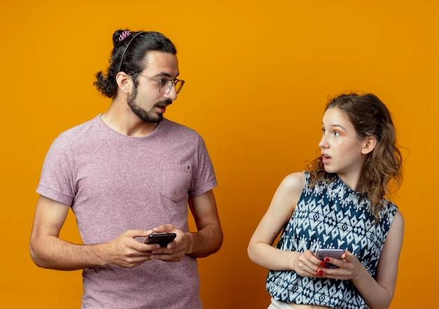 Casal jovem, homem e mulher, olhando um para o outro surpresos, segurando celulares sobre uma parede laranja