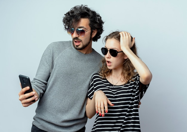 Casal jovem, homem e mulher, parecendo surpreso com a tela do smartphone em pé sobre uma parede branca
