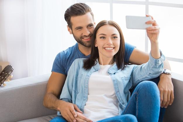 Casal jovem, homem e mulher, se mudando para um novo apartamento juntos, realocação usando um dispositivo digital