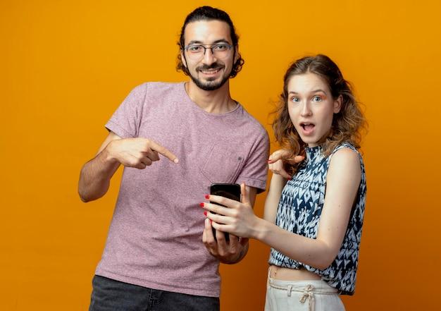 Casal jovem, homem e mulher segurando um smartphone apontando com o dedo para ele, surpreso e feliz sobre a parede laranja