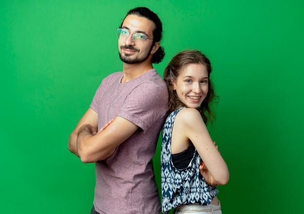 Casal jovem, homem e mulher, sorrindo em pé de costas um para o outro na parede verde