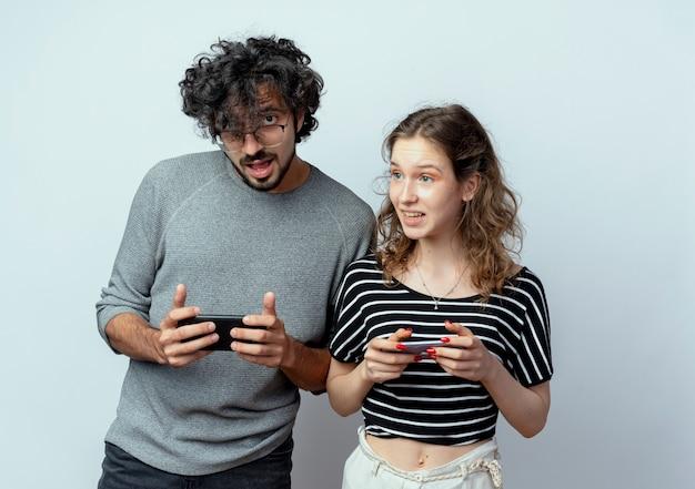 Casal jovem, homem e mulher, sorrindo, segurando seus telefones celulares, em pé sobre um fundo branco