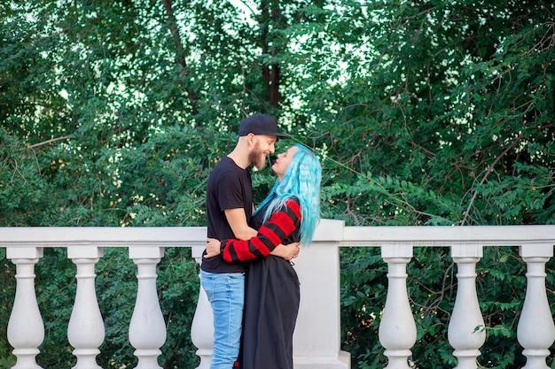 Casal jovem incomum abraçando no parque. juventude informal. mulher com cabelo azul e um cara com barba