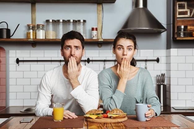 Casal jovem infeliz sentado na cozinha durante o almoço em casa, tendo um problema, cobrindo a boca