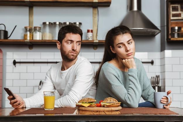 Casal jovem infeliz sentado na cozinha durante o almoço em casa, tendo um problema, segurando um telefone celular