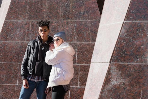 Casal jovem interracial moderno, usando óculos escuros, olhando para a câmera