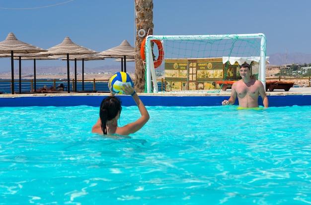 Casal jovem jogando pólo aquático no hotel em um dia ensolarado de verão