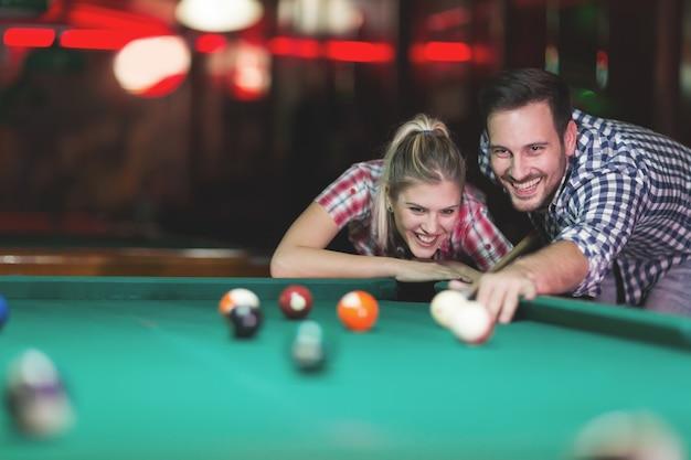Casal jovem jogando sinuca em um bar enquanto se diverte na cidade