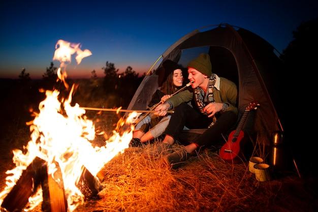 Casal jovem junto com uma fogueira