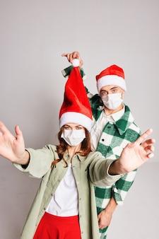 Casal jovem junto máscaras médicas de ano novo, diversão de feliz natal
