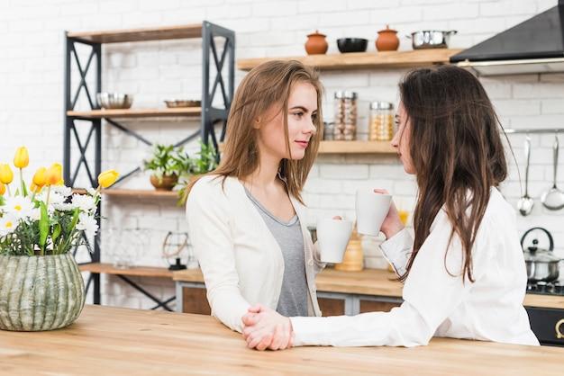 Casal jovem lésbica, segurando a mão do outro, bebendo café em casa
