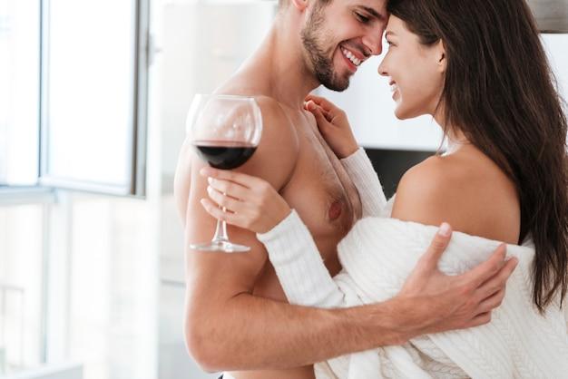 Casal jovem lindo e alegre se abraçando e bebendo vinho tinto em casa