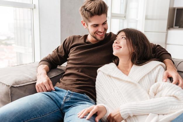 Casal jovem lindo e feliz sentado no sofá em casa juntos
