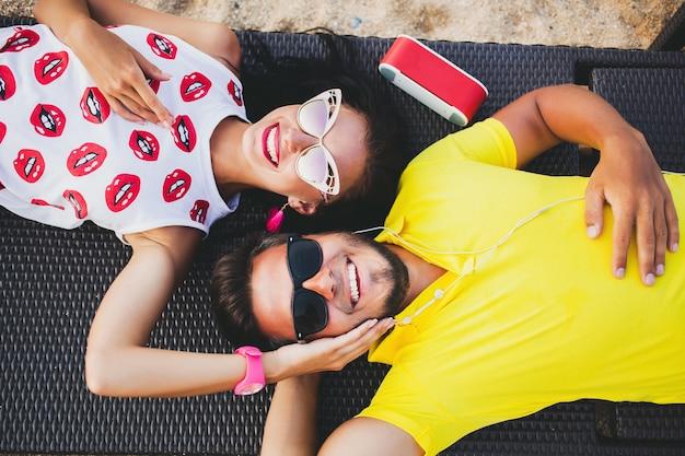 Casal jovem lindo hippie apaixonado, deitado, abraçando, ouvindo música, óculos de sol, roupas elegantes, férias de verão, se divertindo, sorrindo, feliz, colorido, vista de cima