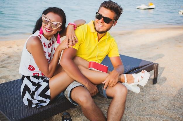 Casal jovem lindo hippie apaixonado, sentado na praia, ouvindo música, óculos de sol, roupa elegante, férias de verão, se divertindo, sorrindo, feliz, colorido, emoção positiva