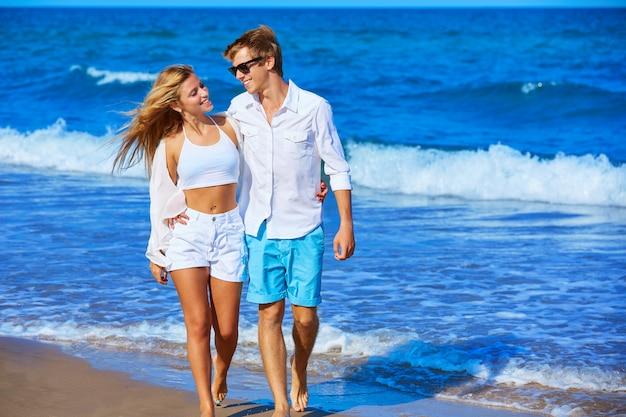 Casal jovem loiro andando na praia