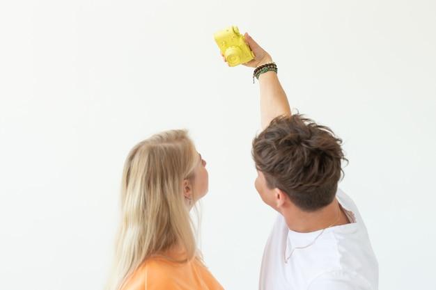 Casal jovem louco engraçado loira e um cara hipster tirando uma selfie em um filme amarelo vintage