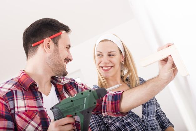 Casal jovem montando prateleira de madeira na parede de sua nova casa