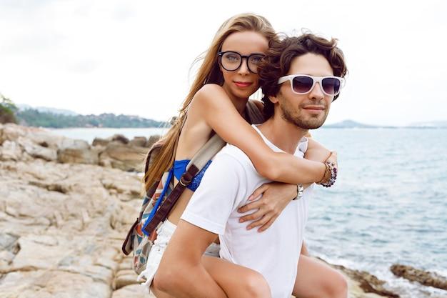 Casal jovem muito elegante hipster apaixonado, se divertindo e abraços na incrível praia de pedra em um dia chuvoso de verão.