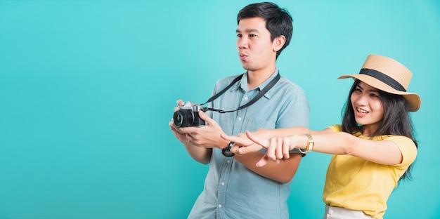 Casal jovem mulher bonita apontar o dedo e homem bonito, segurando a câmera tiro fotografia