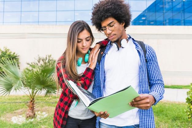 Casal jovem multiétnico juntos lendo o livro de pé contra o edifício da universidade