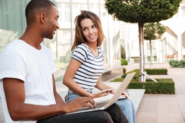 Casal jovem multiétnico sorridente usando laptop e celular ao ar livre