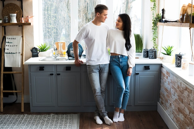 Casal jovem multirracial em pé na cozinha