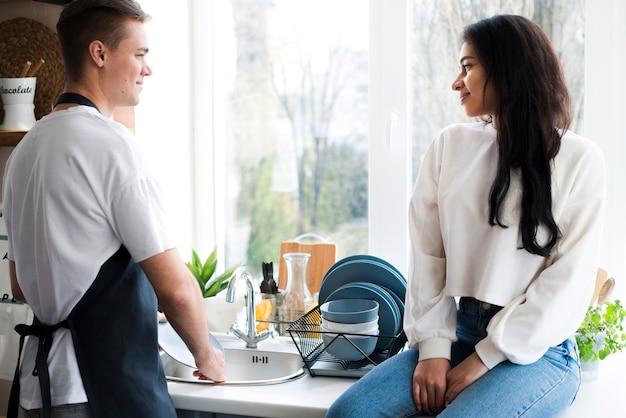 Casal jovem multirracial olhando uns aos outros na cozinha