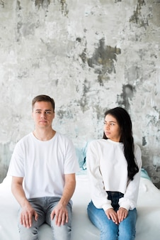 Casal jovem multirracial, sentados lado a lado