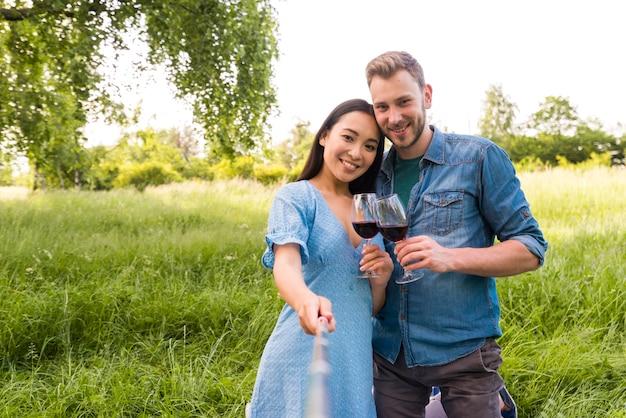 Casal jovem multirracial tomando selfie com taças de vinho