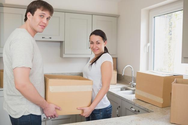 Casal jovem na cozinha segurando caixas móveis