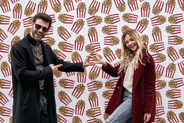 Casal jovem na parede do fundo da parede da marca de rua projetada com comida de rua