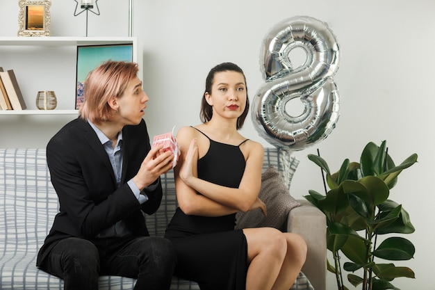 Casal jovem no dia da mulher feliz cara triste dá presentes para mulher rígida sentada no sofá na sala de estar