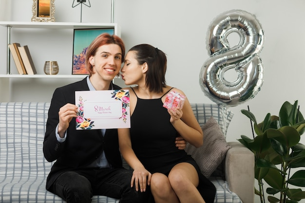 Casal jovem no dia da mulher feliz segurando cartão postal com a presente garota beijando as bochechas de um cara sentado no sofá da sala