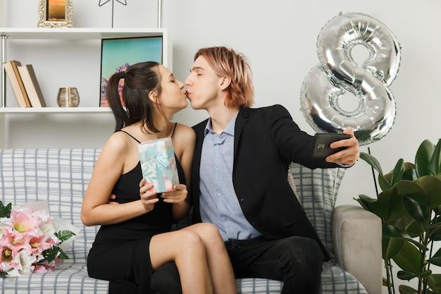Casal jovem no dia da mulher feliz segurando um presente tira uma selfie sentado no sofá da sala