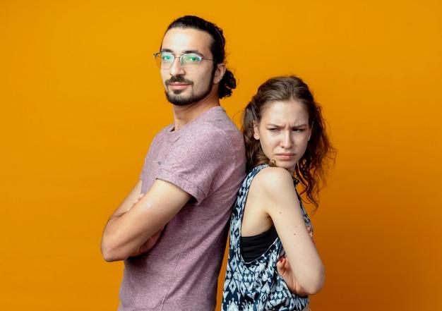 Casal jovem olhando para a câmera de pé, costas com costas e os braços cruzados sobre um fundo laranja