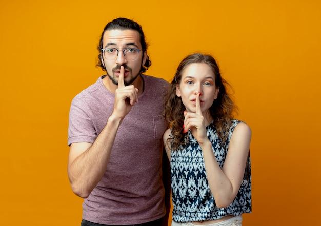 Casal jovem olhando para a câmera fazendo gesto de silêncio com os dedos nos lábios em pé sobre um fundo laranja